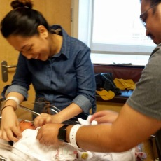 Mom and Dad putting her outfit on because we are about to leave the hospital.